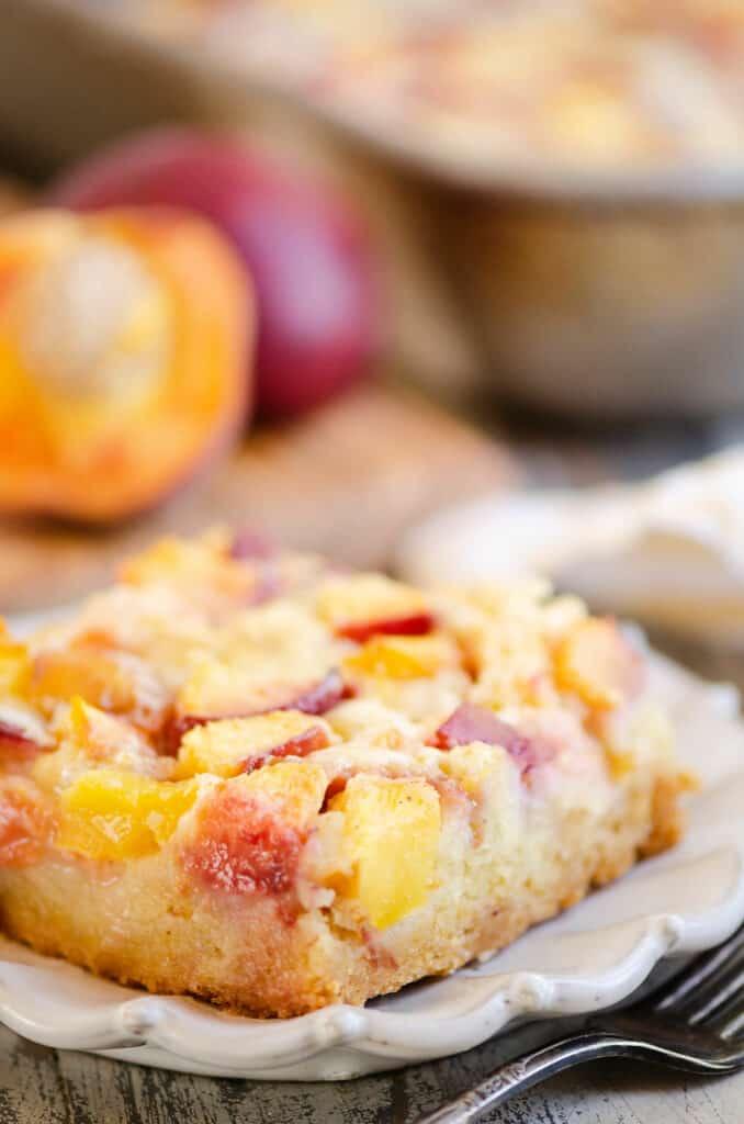 side of slice of peach custard dessert on plate with fresh peaches