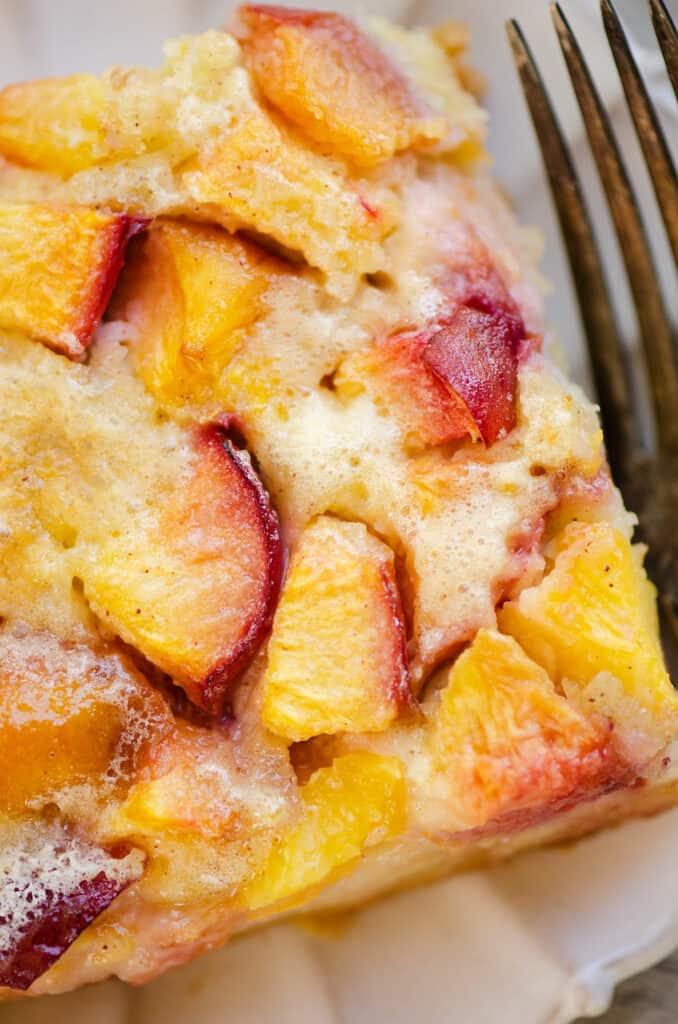 piece of peach custard dessert on plate with fork