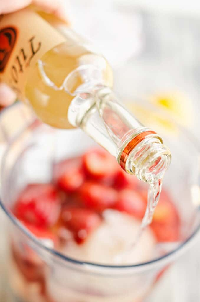 titos vodka poured into blender with strawberries