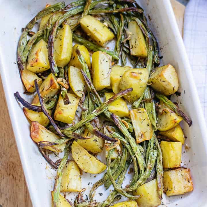 roasted green beans and potatoes in white baking dish