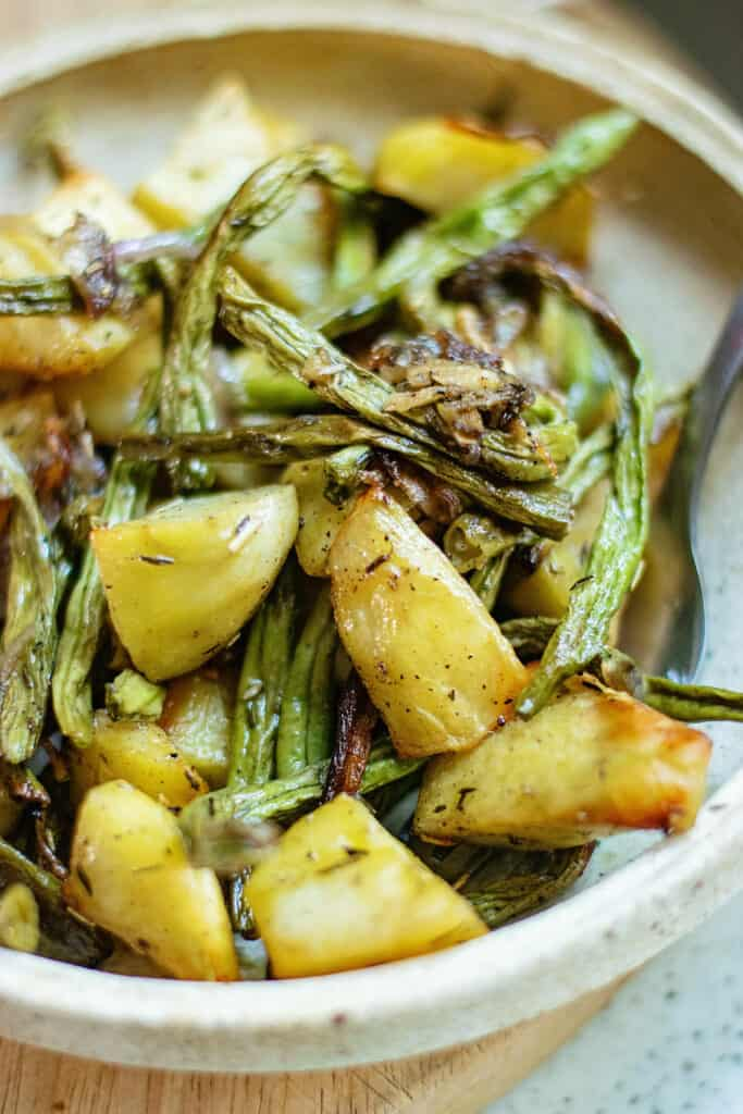 roasted green beans and potatoes on plate with fork