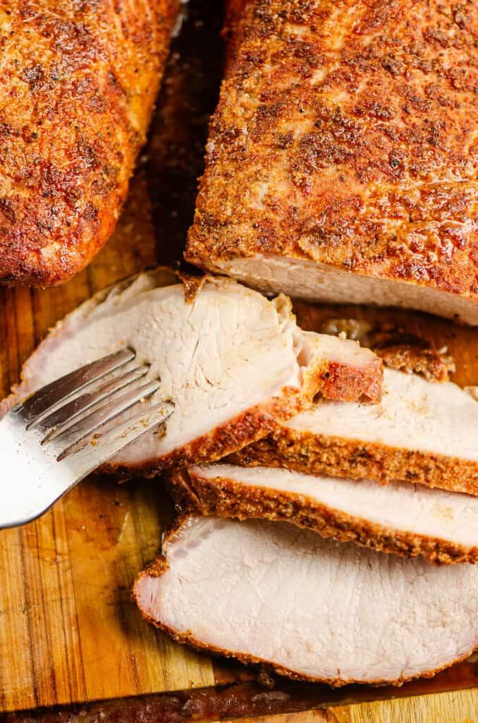 serving fork in slice of pork loin