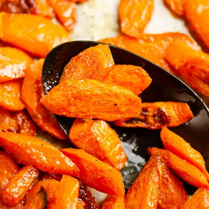 black spoon scooping baked carrots
