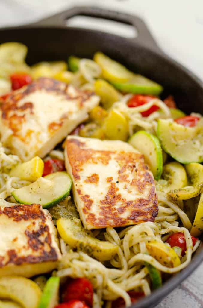 grilled halloumi cheese over vegetables and pesto spaghetti