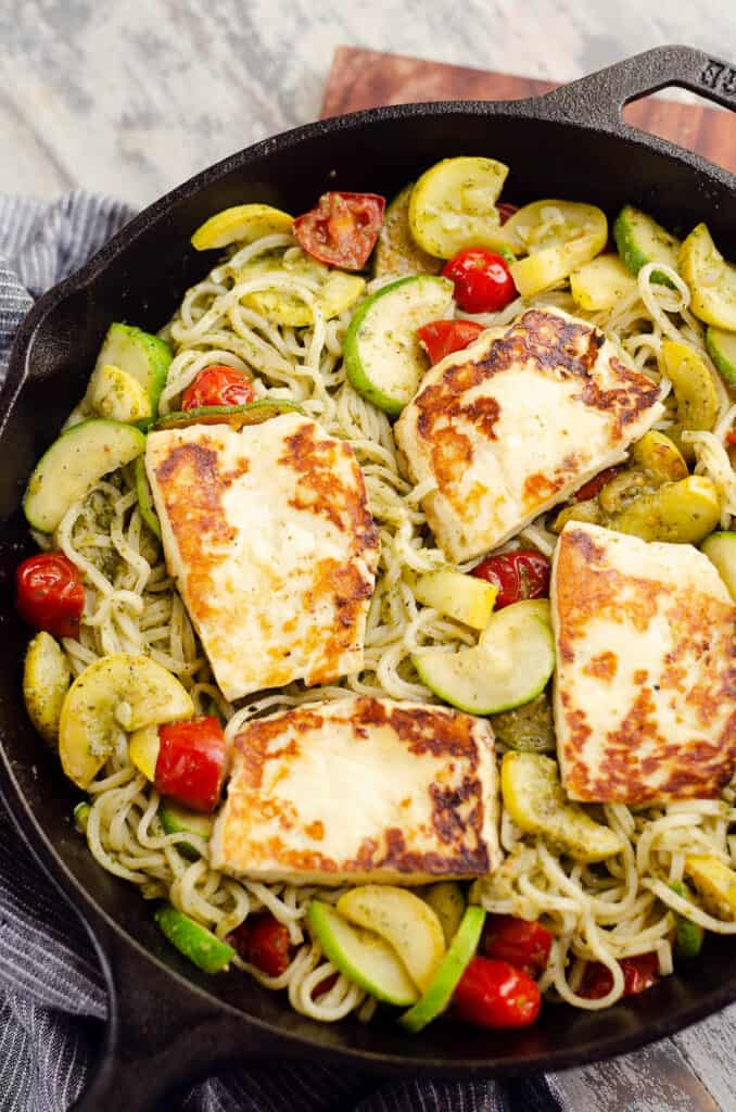 grilled halloumi cheese and pesto vegetable pasta in cast iron pan