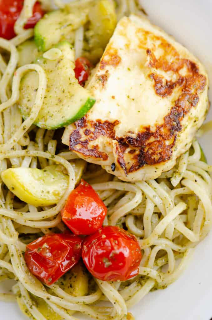 grilled halloumi cheese, vegetables and pesto spaghetti in bowl