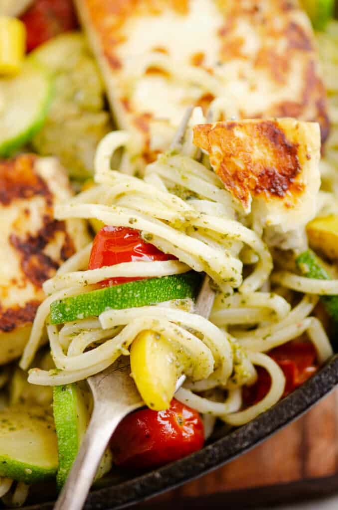 grilled halloumi cheese and vegetable pasta on fork