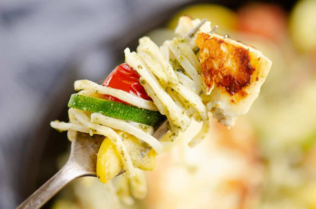 grilled halloumi cheese and vegetable pasta wrapped around fork
