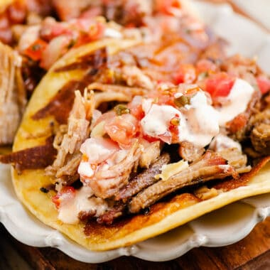 crispy cheese and pork carnitas in flour tortillas on white scalloped plate