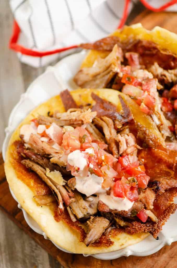pork carnitas tacos on white plate with striped napkin