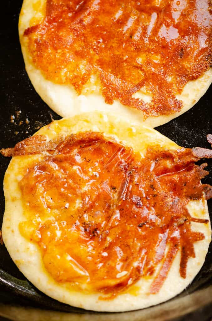 tortillas in cast iron pan topped with crispy cheese