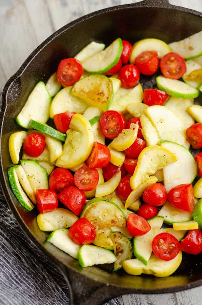 sautéed squash and tomatoes in cast iron pan