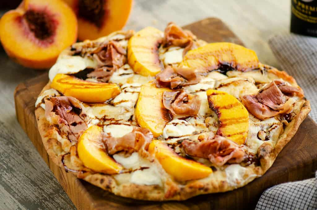 peach and prosciutto pizza with balsamic glaze on cutting board