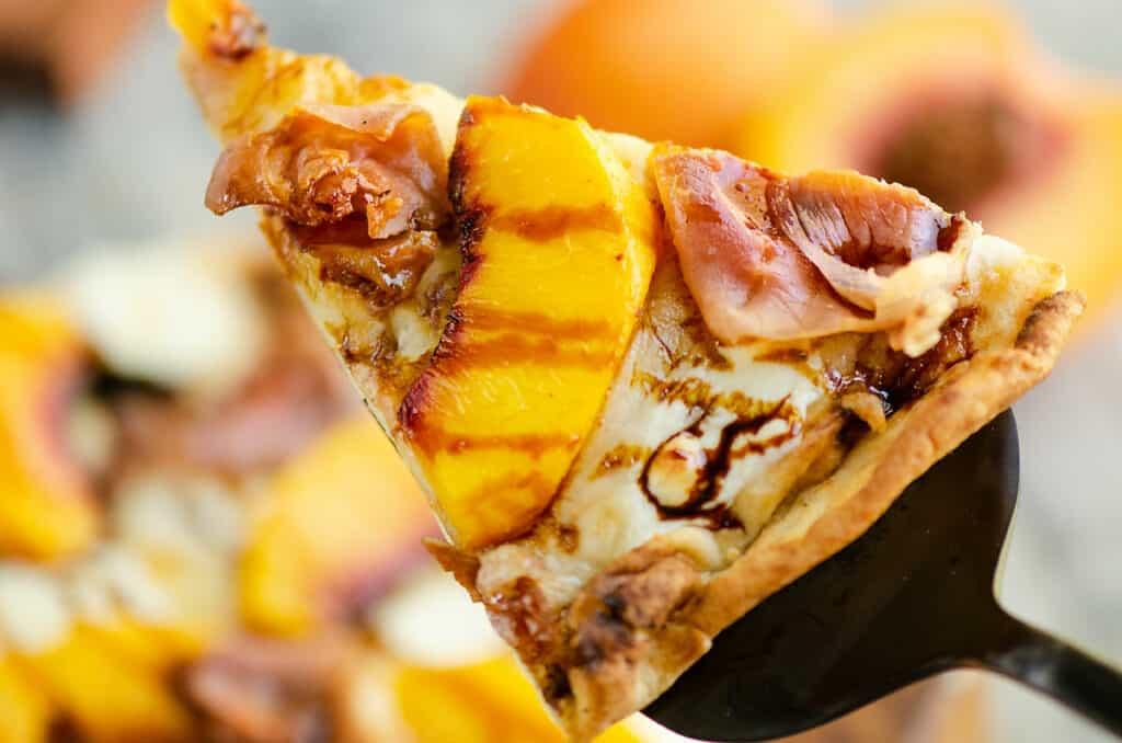 slice of crispy peach and prosciutto pizza