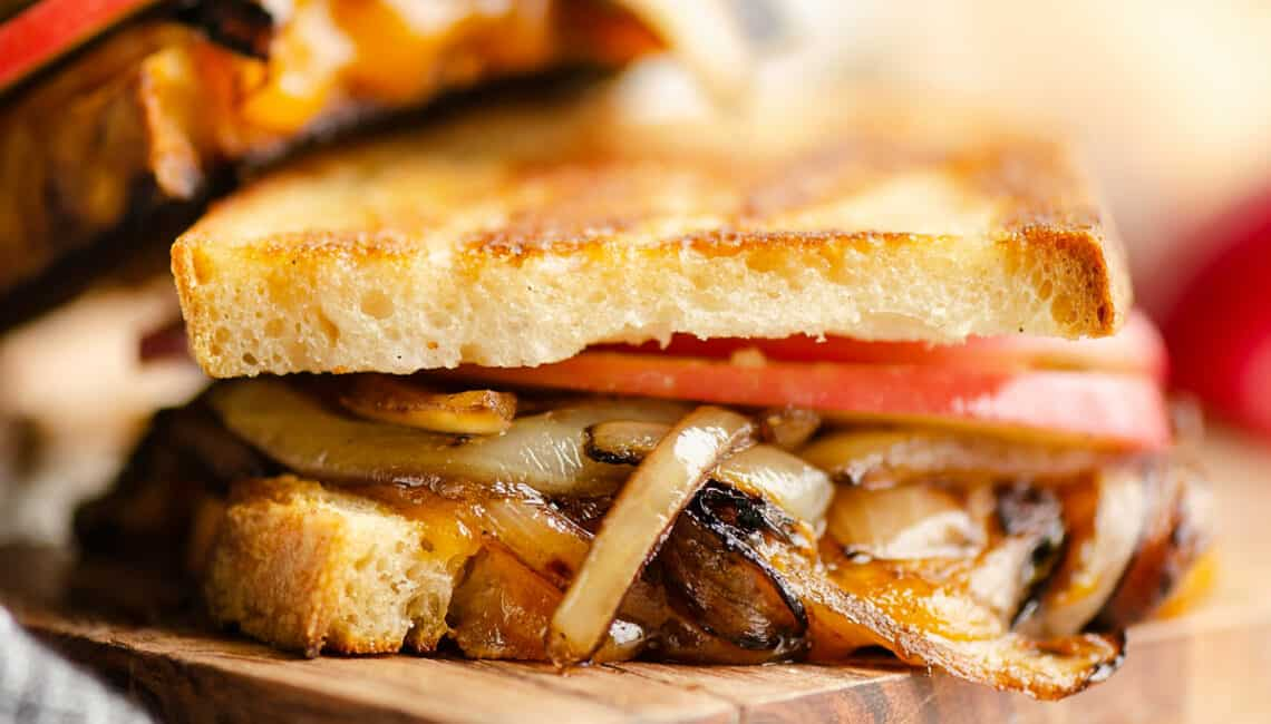 Grilled cheese with apples and balsamic onions on cutting board