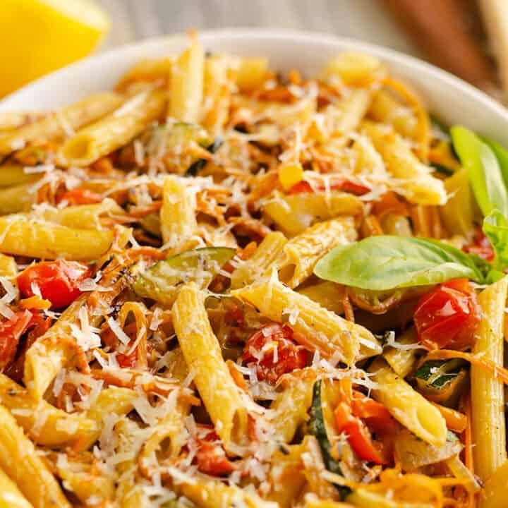 Pasta Primavera in white bowl with fresh basil, lemon and parmesan