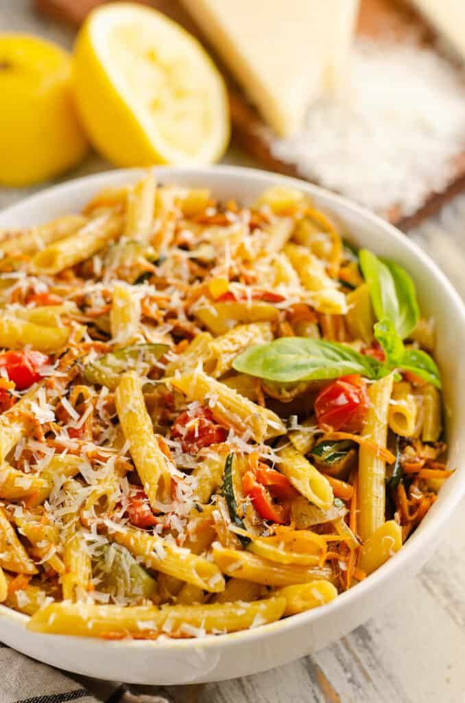 Pasta Primavera in white bowl with fresh basil and lemon