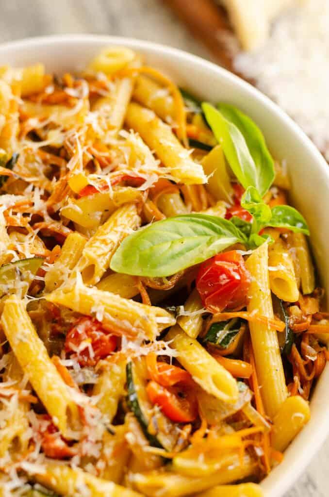 Pasta Primavera in white bowl with fresh basil and parmesan