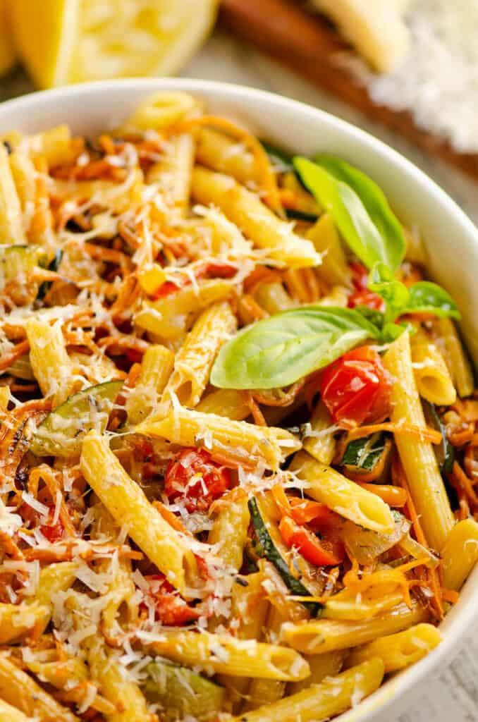 Pasta Primavera in white bowl with fresh basil
