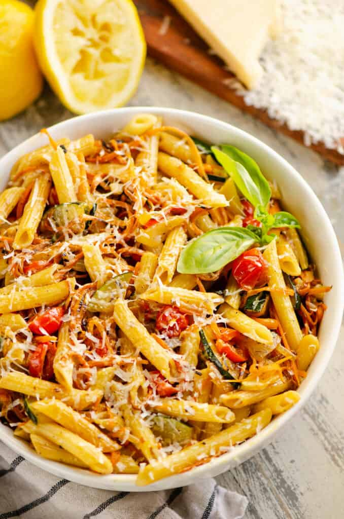 white bowl with Pasta Primavera topped with fresh basil