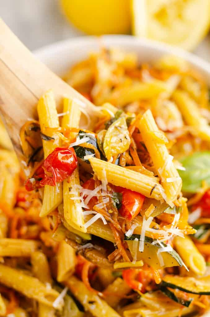 Blackstone Pasta Primavera scooped from bowl with wooden spoon