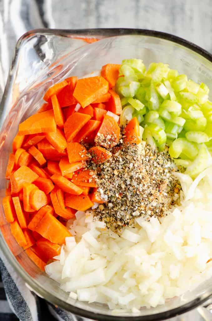 carrots, celery, onions and Greek Freak seasoning in bowl for chicken noodle soup
