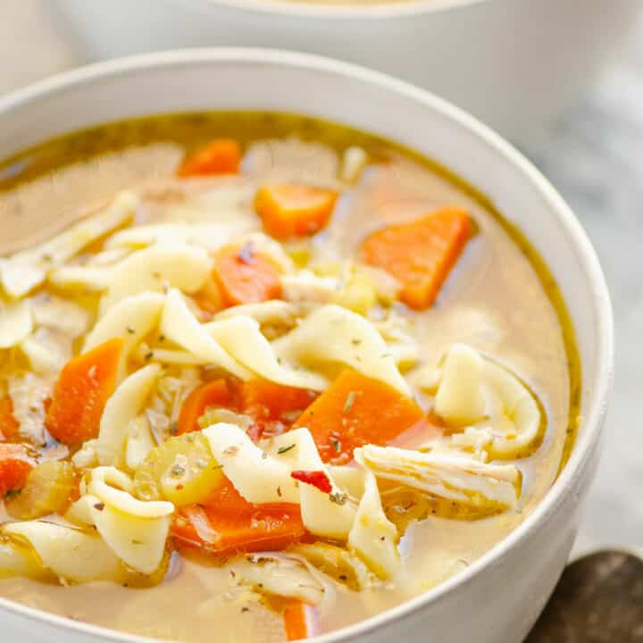 bowl of Greek chicken noodle soup in white bowl