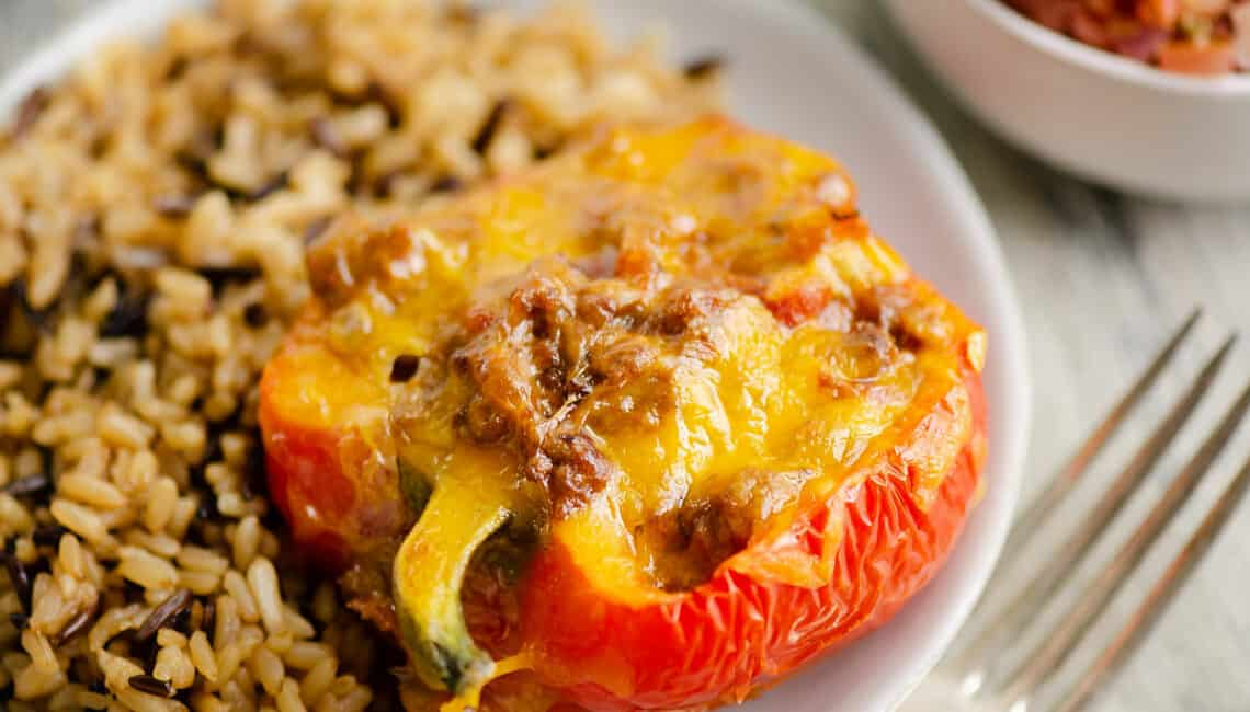 Cheesy Taco stuffed pepper on white plate with rice