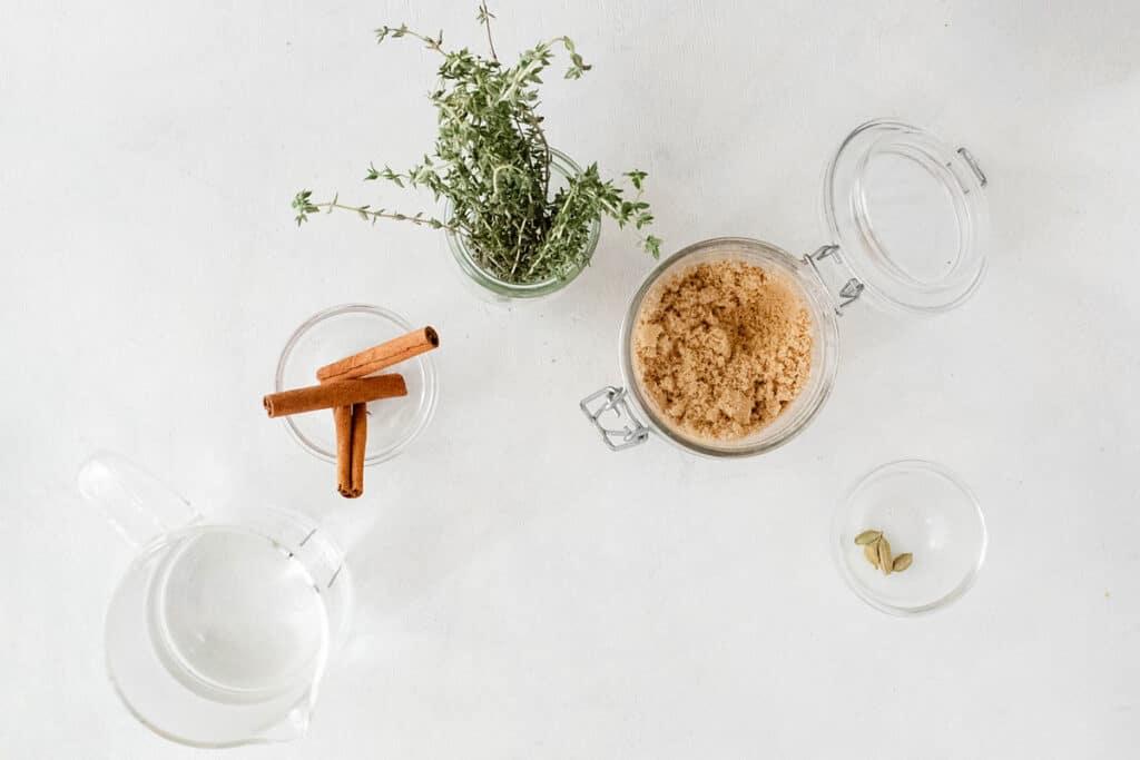brown sugar, cinnamon sticks, thyme and cardamom on white table