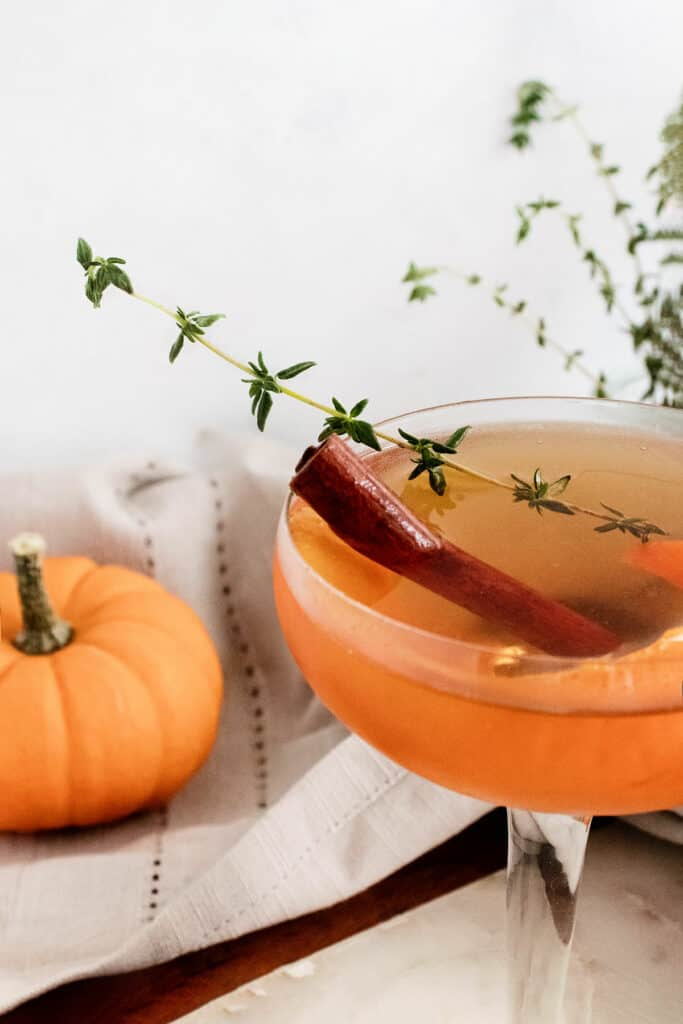 fall spiced old fashioned with cinnamon stick and thyme sprig in glass