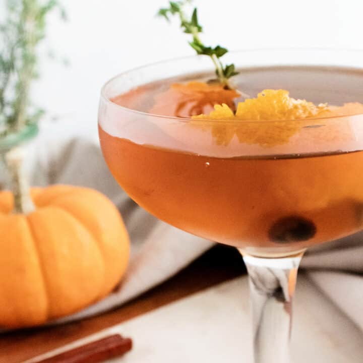 fall spiced old fashioned with orange peel and thyme in glass