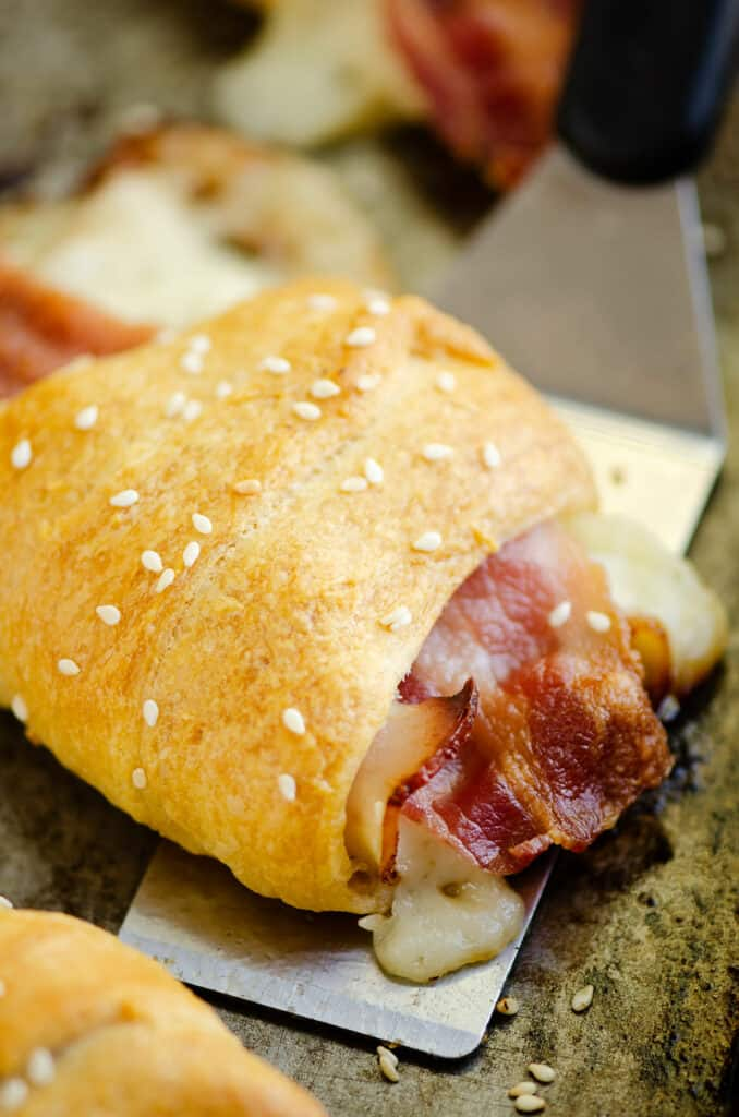 bacon swiss crescent roll topped with sesame seeds